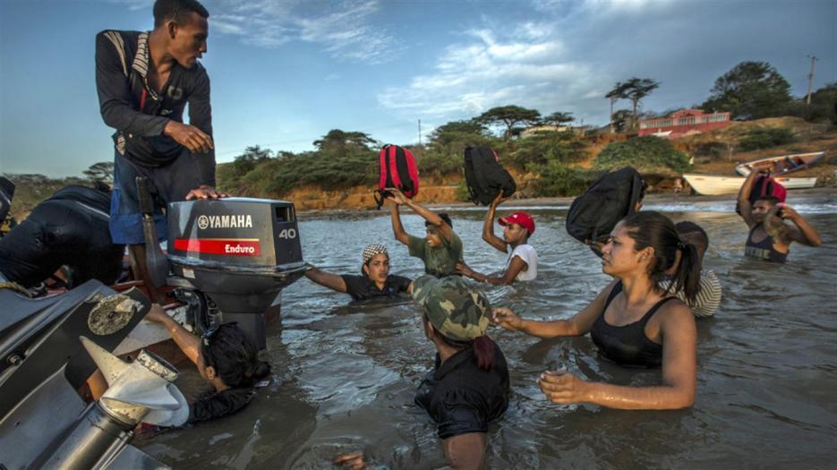 Un grupo de migrantes venezolanos aborda un bote que los llevará hasta la isla de Curaçao Meridith Kohut/NYT