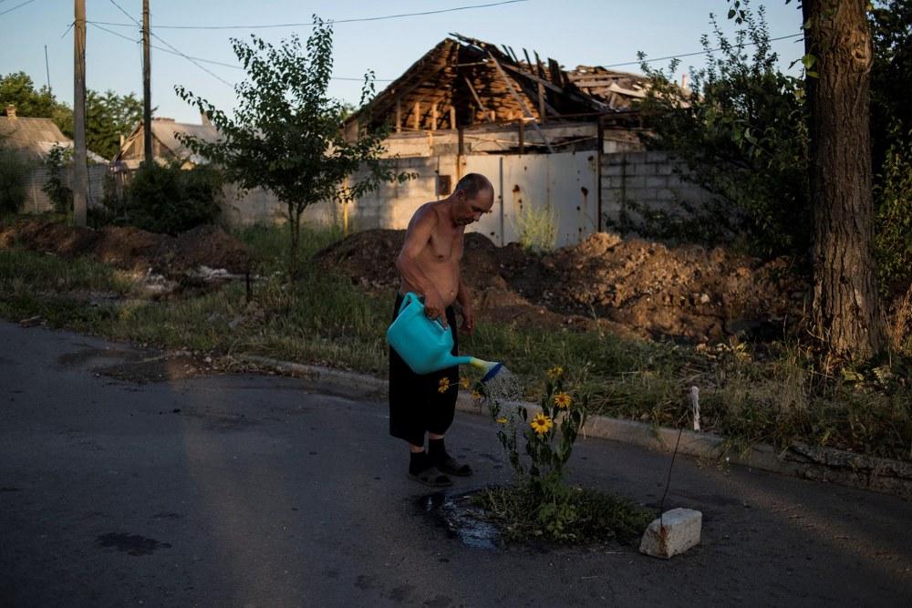 Proyectos a Largo Plazo, primer premio. Un hombre riega las plantas en la ciudad destrozada deSpartak. Valery Melnikov, Rossiya Segodnya