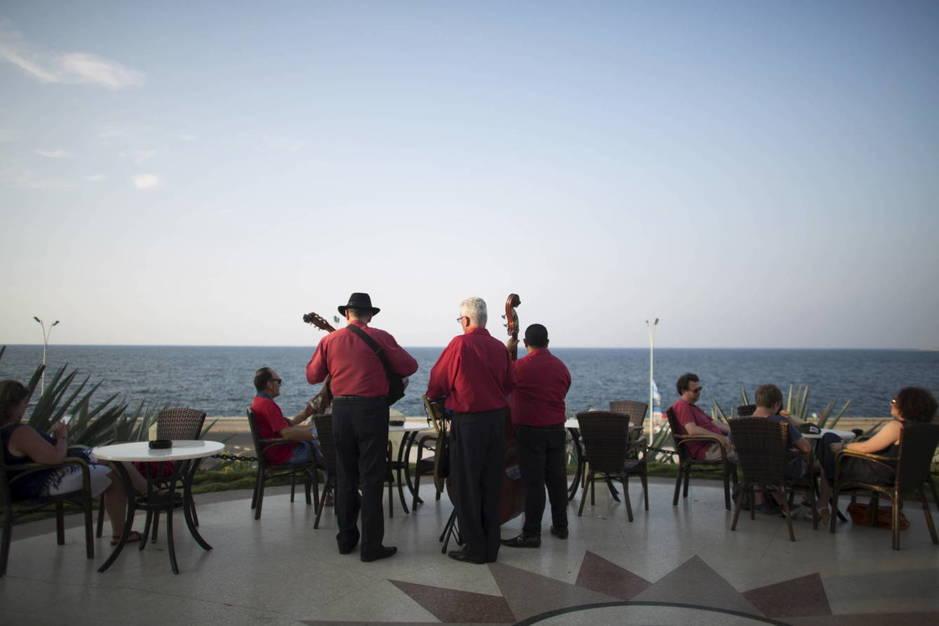 Músicos cubanos tocan temas tradicionales mientras unos turistas disfrutan del atardecer en un hotel de La Habana (Reuters).