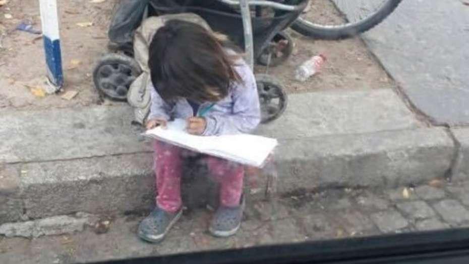 Una nena hace la tarea mientras pide limosna