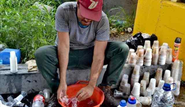 Venezuela :Este hombre, en situación de calle, lava vasos plásticos con vinagre y agua del Guaire para revenderlos (FOTOS)