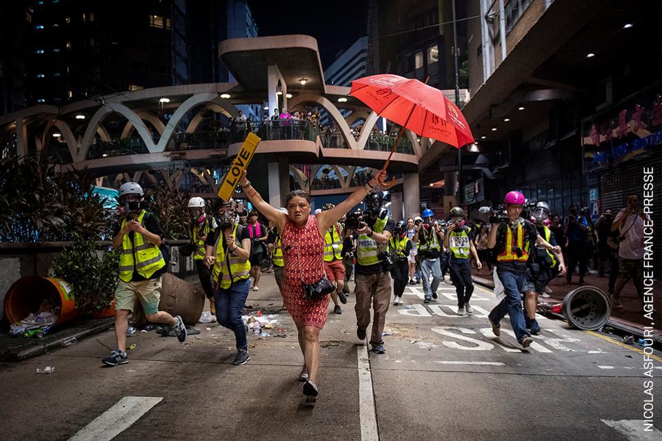 Una mujer levanta un paraguas (un símbolo de protesta)