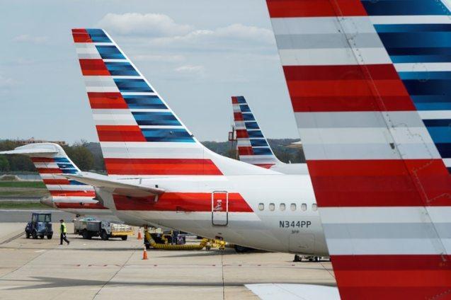 Un miembro de un equipo de tierra pasa junto a los aviones de American Airlines estacionados en la puerta durante el brote de coronavirus en el Aeropuerto Nacional Ronald Reagan en Washington (Reuters)