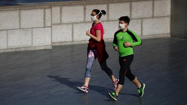 La gente corre con máscaras protectoras a orillas del río Támesis, mientras continúa la propagación de la enfermedad coronavirus (COVID-19), Londres