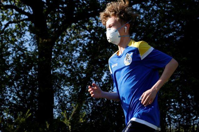 Un joven corre con barbijo en Bristol, Reino Unido (Reuters)