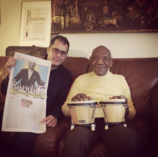 Cándido con el periodista Luis Leonel León, quien sostiene la portada de un reportaje que Diario Las Américas le dedicó como homenaje a su trayectoria.