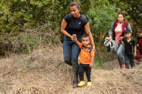 Los migrantes ilegales se acercan a los funcionarios encargados de hacer cumplir la ley después de que fueron introducidos de contrabando en los Estados Unidos para intentar solicitar asilo en Rincon Village cerca de McAllen, Texas, el 24 de marzo de 2021 (Kaylee Greenlee - Daily Caller News Foundation).