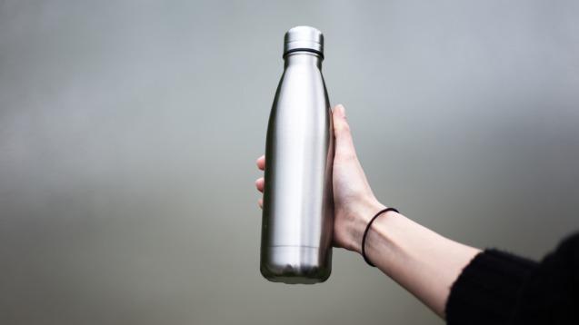 Mano sosteniendo una botella de metal