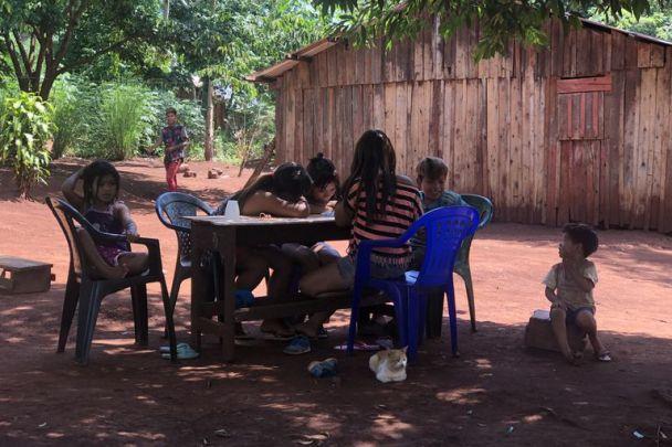 En la comunidad Yryapú, en Iguazú, Misiones, los chicos hacen la tarea de la escuela a la sombra. Como no tienen conectividad, usan cuadernos y fotocopias.