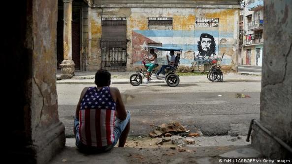 Un hombre vestido con una camiseta sin mangas con un diseño de la bandera estadounidense se sienta en la puerta de un edificio decrépito en La Habana y observa un riksha pasar